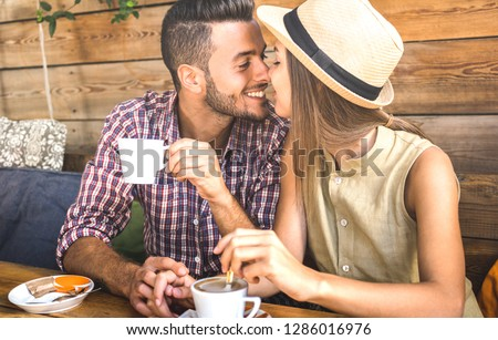 Young fashion lovers couple at beginning of love story - Handsome man kissing beautiful woman at coffee shop bar - Relationship concept with happy boyfriend and girlfriend together - Warm retro filter #1286016976