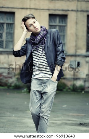 young fashion man in casual wear. posing on the street.