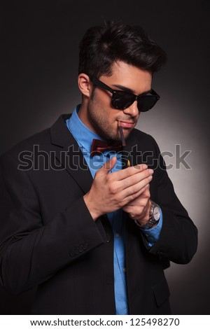 young fashion man lighting his cigarette on black background