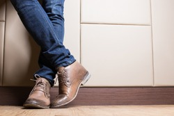 Young fashion man's legs in blue jeans and brown boots on wooden floor