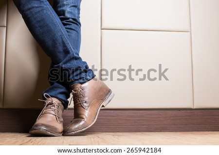 Young fashion man's legs in blue jeans and brown boots on wooden floor #265942184