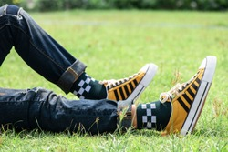 Young fashion man's legs in blue jeans and yellow sneakers on green grass.