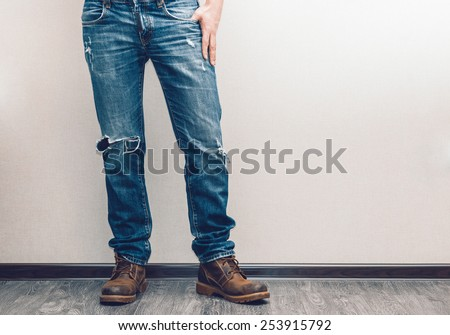 Young fashion man\'s legs in jeans and boots on wooden floor