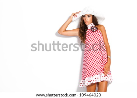 young fashion model in summer dress and hat studio white