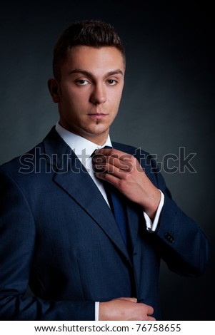 young fashion model man adjusting his tie