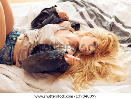 Young fashion sensual young woman lying on the bed in sexy jeans west. Smoking cigarette
