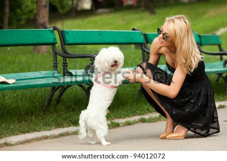 young fashion woman in the park, playing with her dog - stock photo