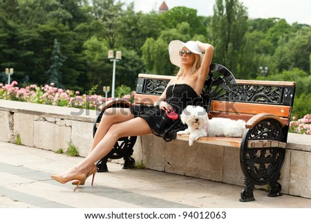 young fashion woman in the park with her dog, sitting on the bench