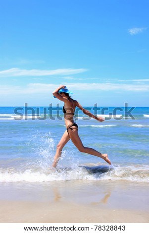 Young fashion woman running on the beach