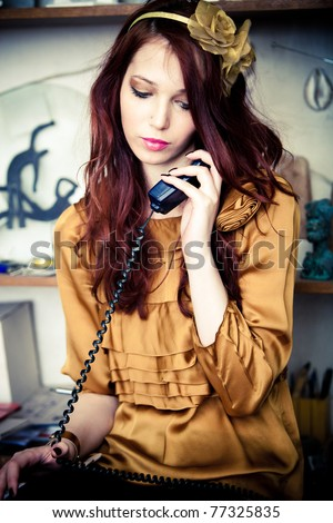 young fashion woman talking on home phone with someone, indoor shot