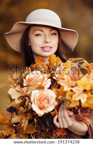 Young fashion woman  walking in autumn park with a bouquet of fall leaves of maple and oak autumn roses.