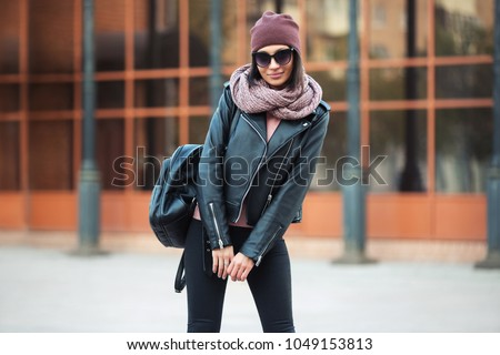 Young fashion woman with backpack walking in city street Stylish female model in leather jacket and black jeans outdoor