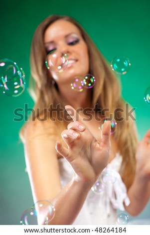 Young fashion woman with soap bubbles. Focus on hand.