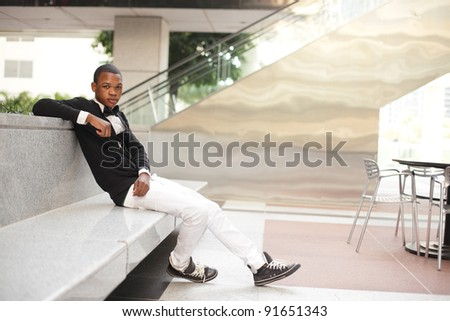 Young fashionable black model sitting on a concrete bench