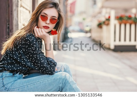 Young fashionable girl wearing red sunglasses, polka dot shirt, posing in street of European city. Copy, empty space for text