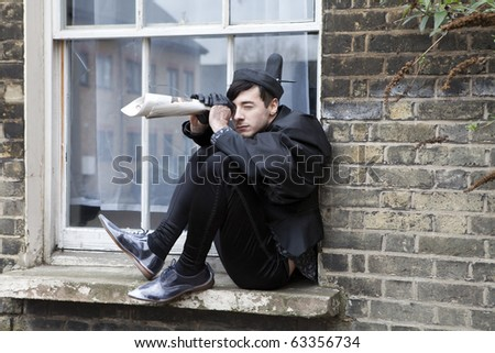 young fashionable man sitting on window-sill and looking down