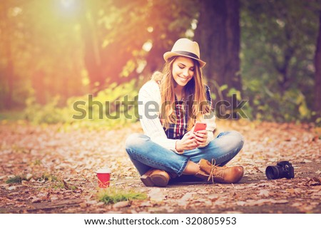 Young fashionable teenage girl with smartphone, camera and takeaway coffee in park in autumn sitting at smiling. Trendy young woman in fall in park texting. Retouched, vibrant colors.