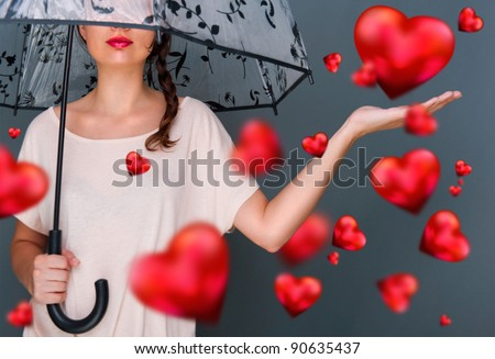 Young fashionable woman holding umbrella standing against grey background red hearts are floating around her. Love rain on Saint Valentine`s Day concept