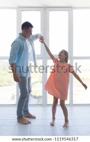 Young father and a little daughter dancing at home - Shutterstock ID 1119546317