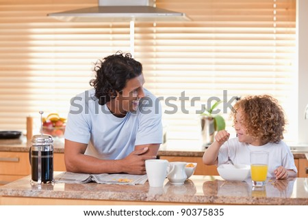 Young father and daughter having breakfast in the kitchen