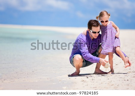 Young father and his adorable little daughter on tropical beach