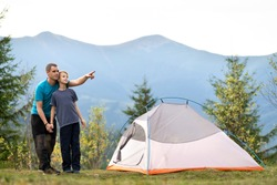 Young father and his child son hiking together in summer mountains. Active family on camping trip.