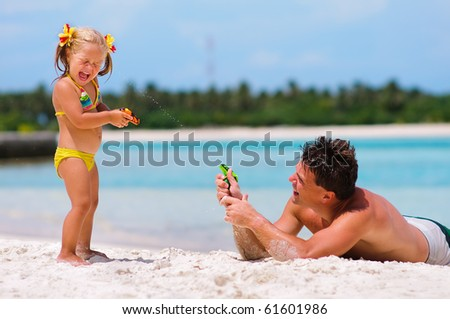 young father and his cute little daughter playing with water guns on exotic beach