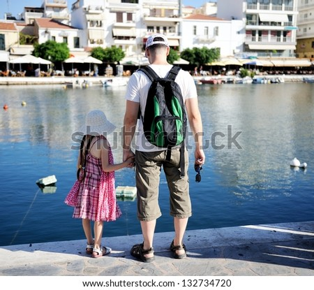 Young father and his daughter looking at the lake