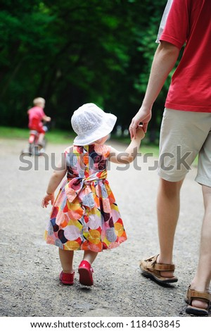 Young father and his little daughter walking in the park. Little  son is riding a bicycle