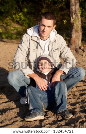 Young father and his little son are sitting and looking at the camera