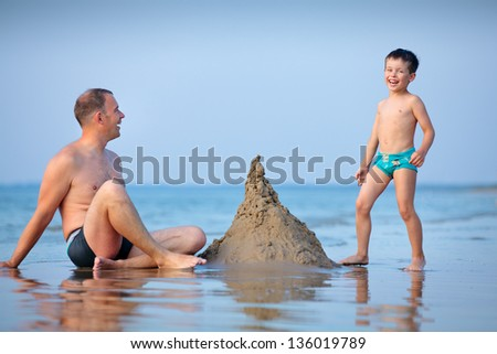 Young father and his little son building sand castle at beach