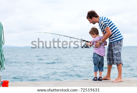 Young father and his son fishing together from wooden jetty