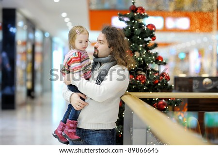 Young father and his toddler girl in shopping mall on Christmas