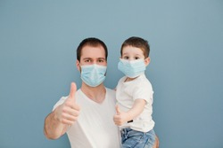 young father and his toddler son wearing surgical masks giving thumbs up to protection during the quarantine on a blue background