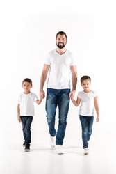 young father and kids holding hands while walking together isolated on white
