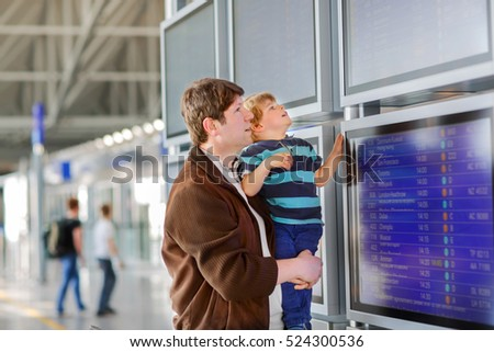 Young father and little son, cute child at the airport. Little kid boy and dad, family traveling together, going on vacation via airplane and checking in at electronic board terminal. #524300536