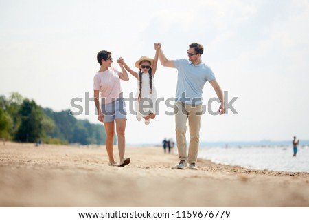 Young father and mother lifting their little daughter over sandy beach while playing during walk #1159676779