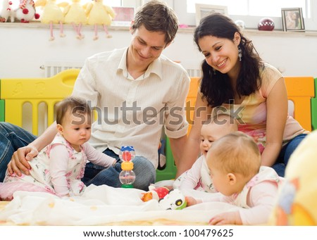 Young father and mother playing with children at home