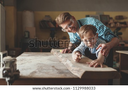 Young father and son at work in carpentry