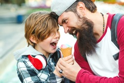 Young father and son enjoying icecream and having fun together. Happy emotional family outdoors. Vacation, summer time, walking at city. Father playfully tries to eat icecream.
