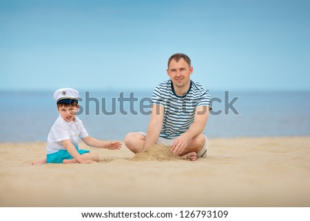 Young father and son playing on the beach
