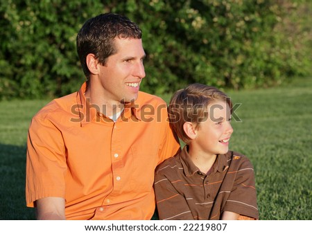 young father and son sitting together outdoors - stock photo
