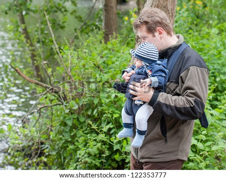 Young father carrying son in sling rucksack in spring park