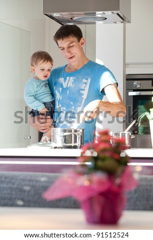 Young father cooking with his baby son in a modern kitchen.