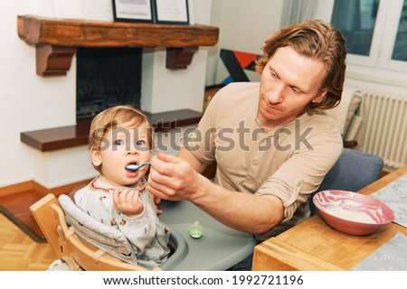 Young father feeding adorable toddler girl with funny facial expression, baby sitting in high chair, dinner time