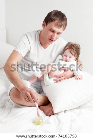 young father feeding his his six months old daughter on the bed at home