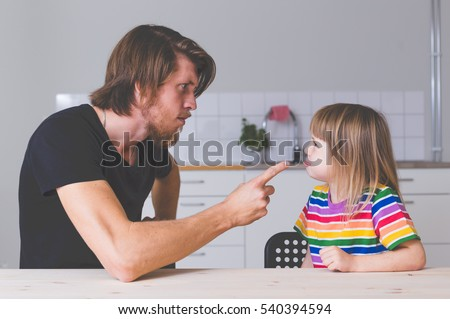 young father fighting with daughter in preschool age, screaming and talking strict with her at home on kitchen