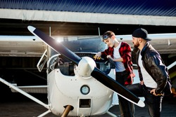 young father giving instructions to his son how to make check up service on place for small propeller airplanes, boy standing with pliers above opened engine compartment.