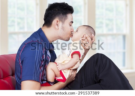 Young father holding his baby on sofa and kiss the baby\'s lips, shot at home