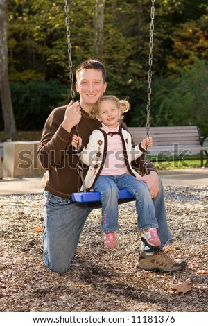 Young father kneeling by little daughter on swing at Cascade Park, Bloomington, IN.